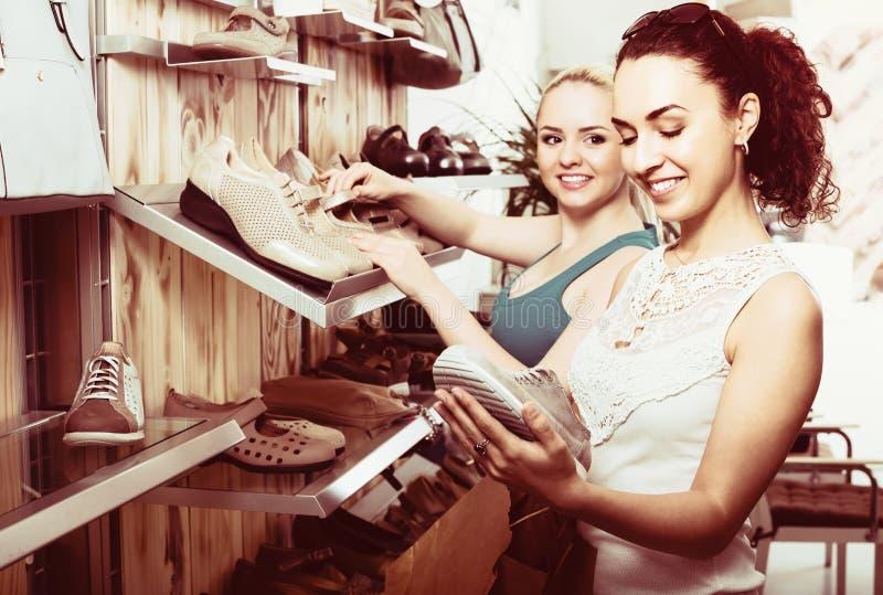 Twee meisjes die schoenen in de opslag kiezen stock fotografie
