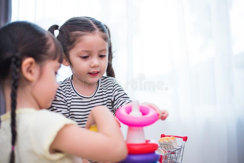Twee meisjes die stuk speelgoed hoepels in huis samen spelen Onderwijs en Geluklevensstijlconcept Het grappige leren en Kinderen stock afbeeldingen