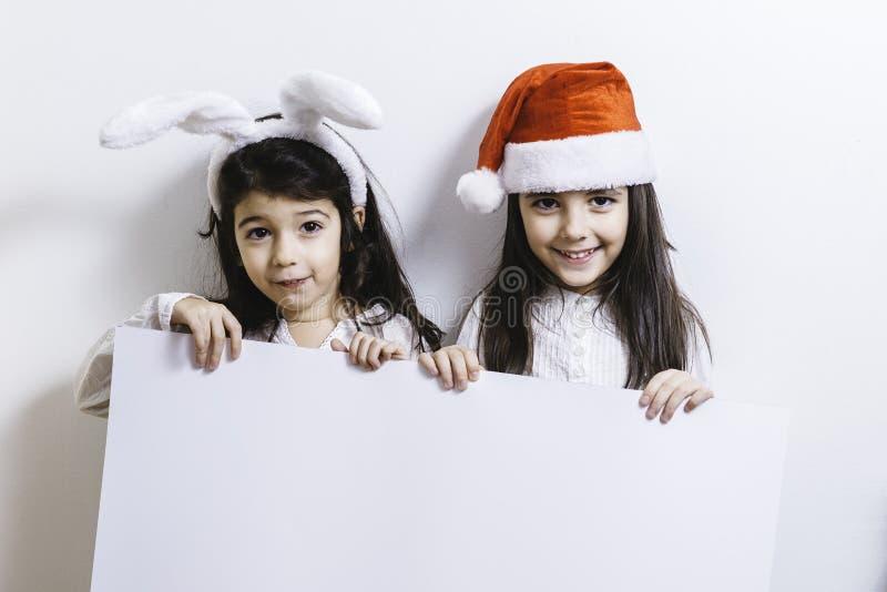 Twee meisjes die voor Kerstmis en Nieuwjaarvakantie stellen royalty-vrije stock afbeeldingen