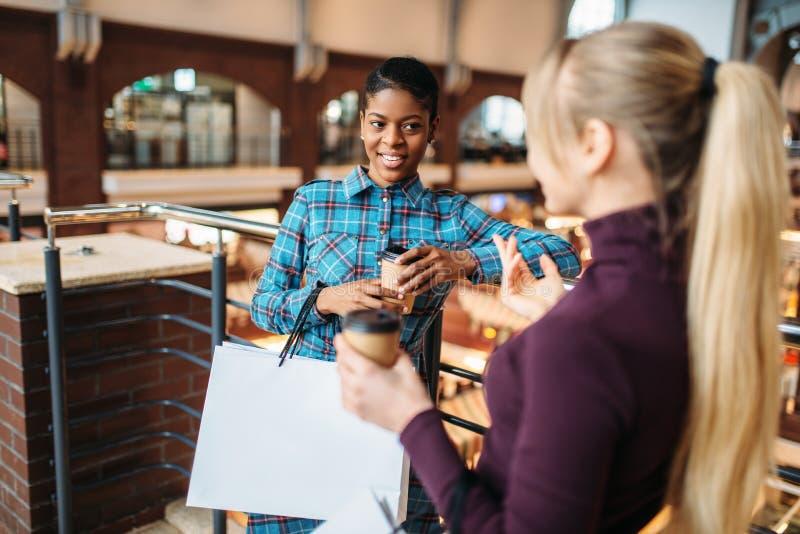 Twee meisjes drinkt koffie na het winkelen stock afbeelding