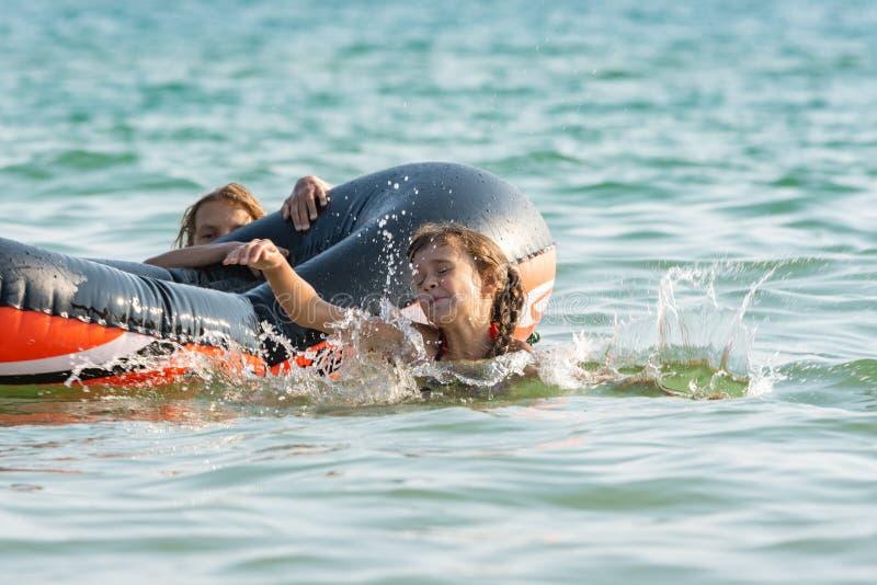 Twee meisjes duiken van een opblaasbare boot in het overzees stock foto