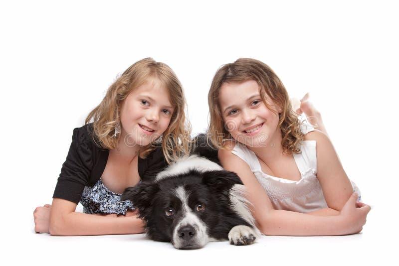 Twee meisjes en een hond stock afbeeldingen