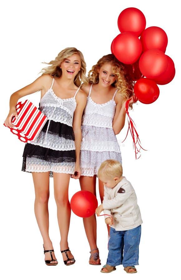 Twee meisjes en een kleine jongen met ballons. stock foto