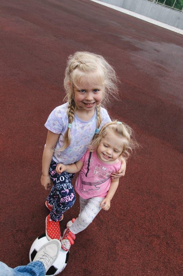 Twee meisjes en een voetbalbal stock foto's