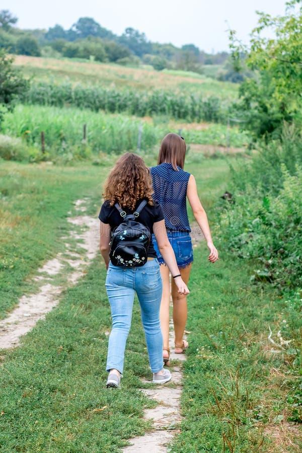 Twee meisjes gaan op een landweg De zomerreis in countryside_ royalty-vrije stock foto