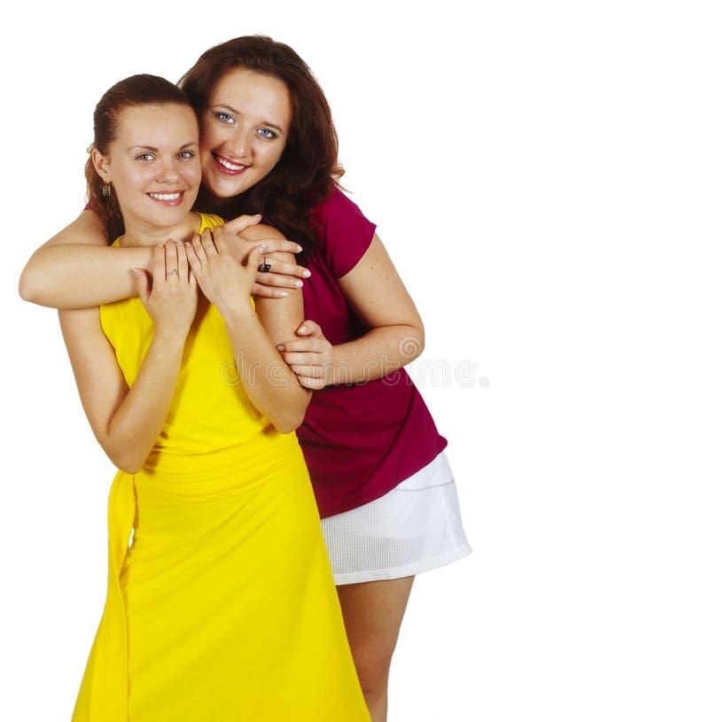 Twee meisjes glimlachen en omhelst stock foto