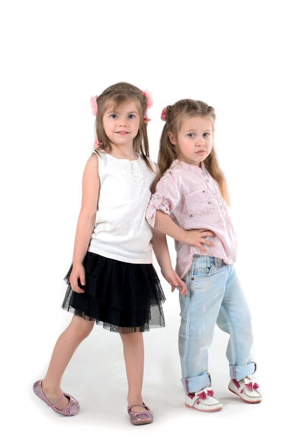 Twee meisjes het blonde in een overhemd en jeans op witeachtergrond royalty-vrije stock afbeeldingen