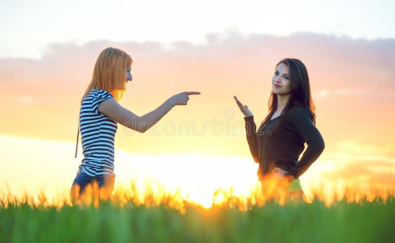 Twee meisjes het debatteren richtend een vinger en negerend in de aard stock fotografie