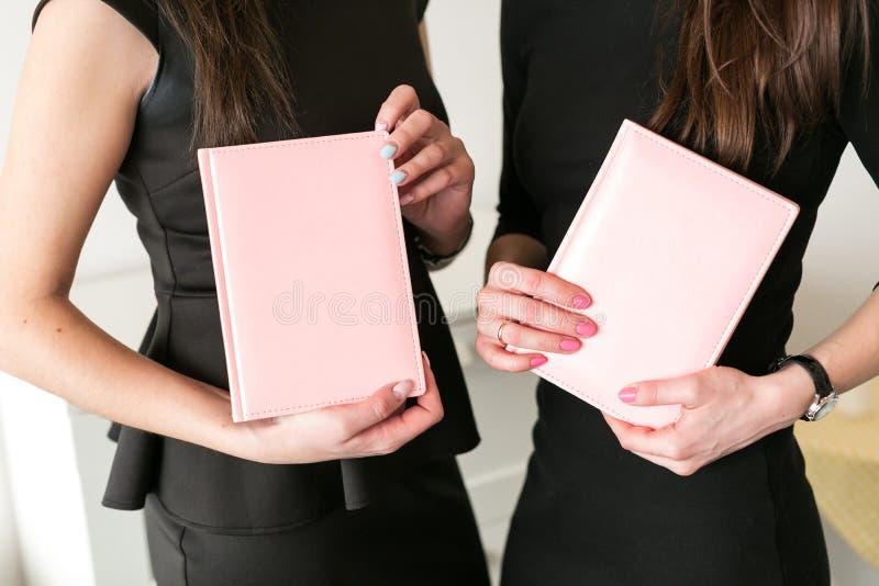 Twee meisjes houden bedrijfsnotitieboekjes in hand stock foto's