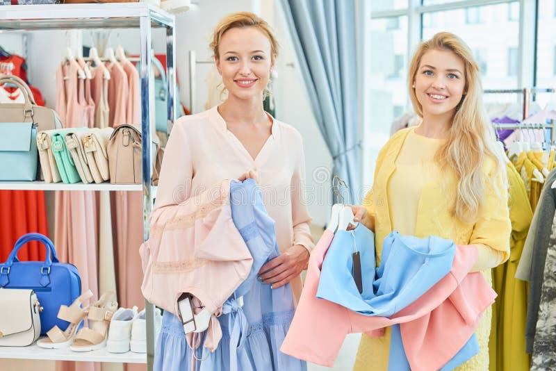 Twee meisjes in kleding slaan op royalty-vrije stock fotografie