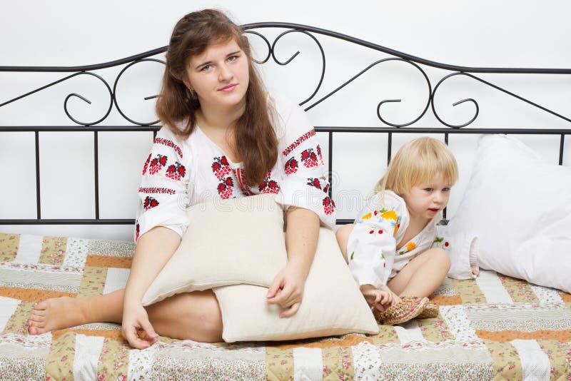 Twee meisjes kleedden zich in Oekraïener op het bed royalty-vrije stock foto