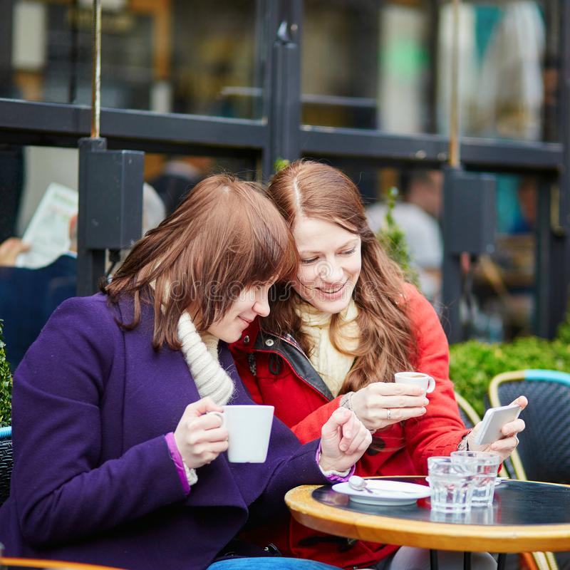 Twee meisjes in koffie het drinken koffie en het gebruiken van mobiele telefoon in Parijs, Frankrijk royalty-vrije stock afbeeldingen
