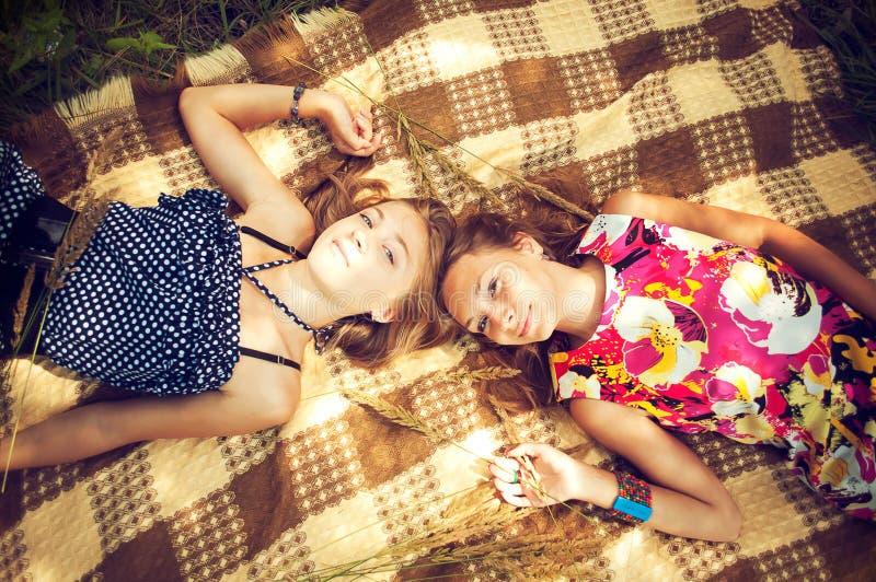 Twee meisjes liggen op cheked uitgespreid stock foto
