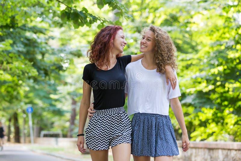 Twee meisjes lopen omhelst bij park royalty-vrije stock fotografie