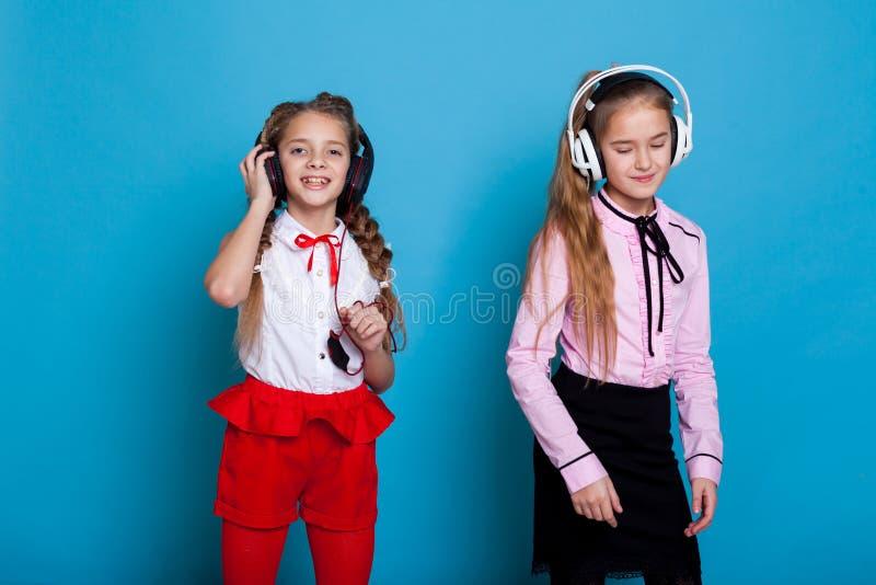 Twee meisjes luisteren aan muziek met hoofdtelefoons en dans royalty-vrije stock foto