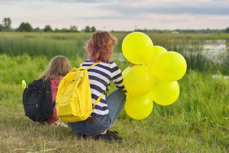Twee meisjes met ballons terug in aard, kinderen dichtbij het meer stock afbeeldingen