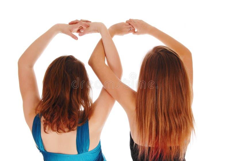 Twee meisjes met daar overhandigt omhoog royalty-vrije stock foto