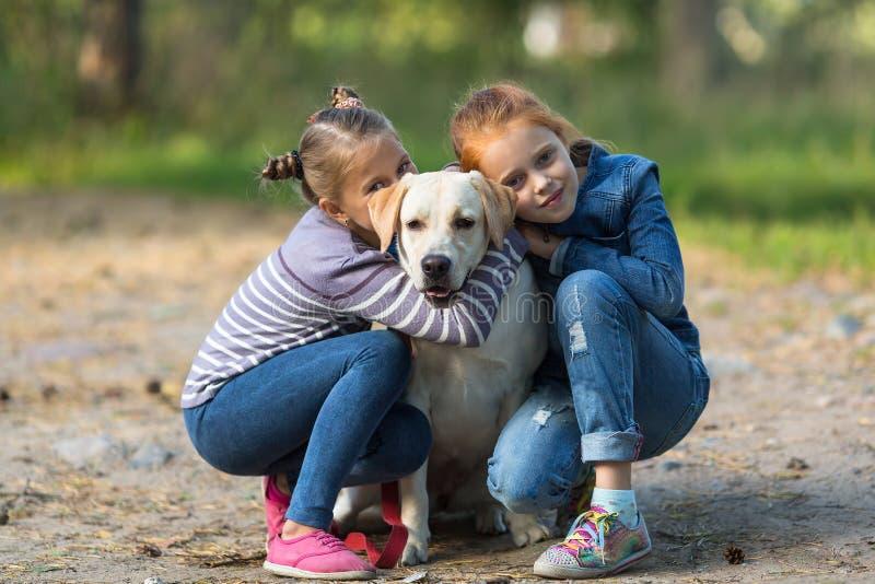 Twee meisjes met de hond in openlucht spelen stock afbeeldingen