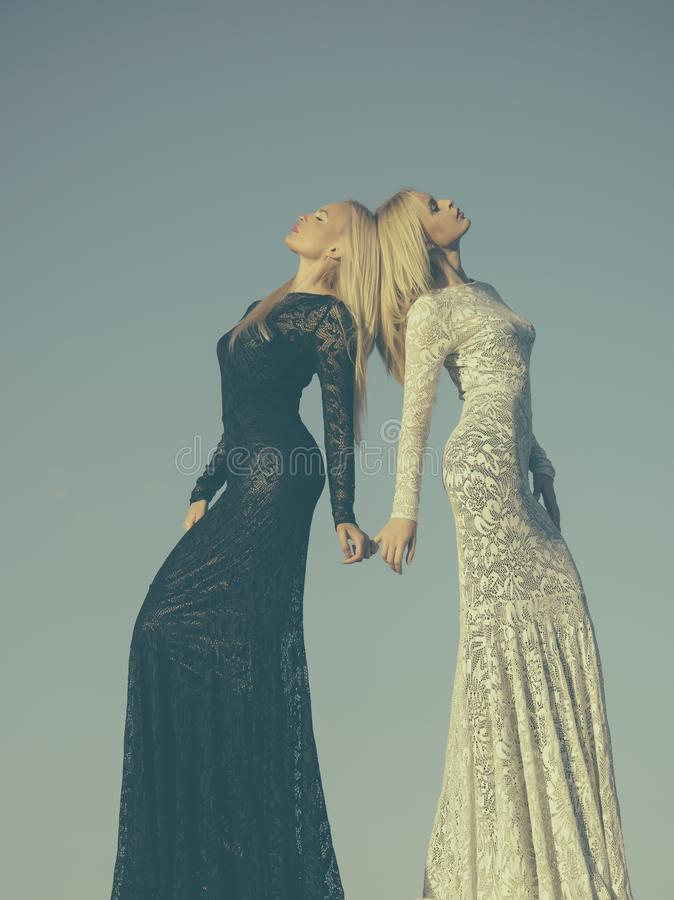 Twee meisjes met het lange blonde haar stellen op grijze hemel royalty-vrije stock fotografie