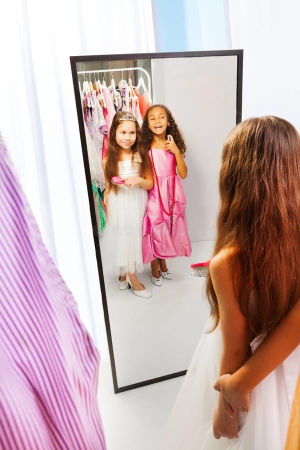 Twee meisjes met kleding in de spiegel stock afbeeldingen