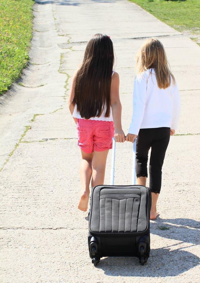 Twee meisjes met koffer stock afbeeldingen