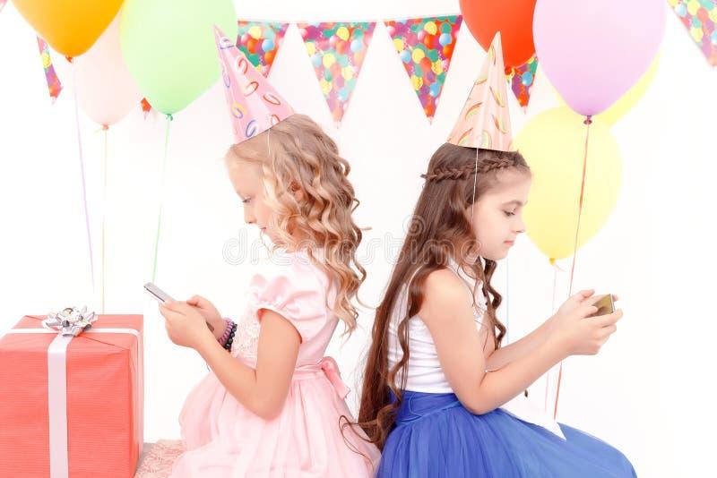 Twee meisjes met mobiele telefoon tijdens verjaardagspartij stock afbeelding