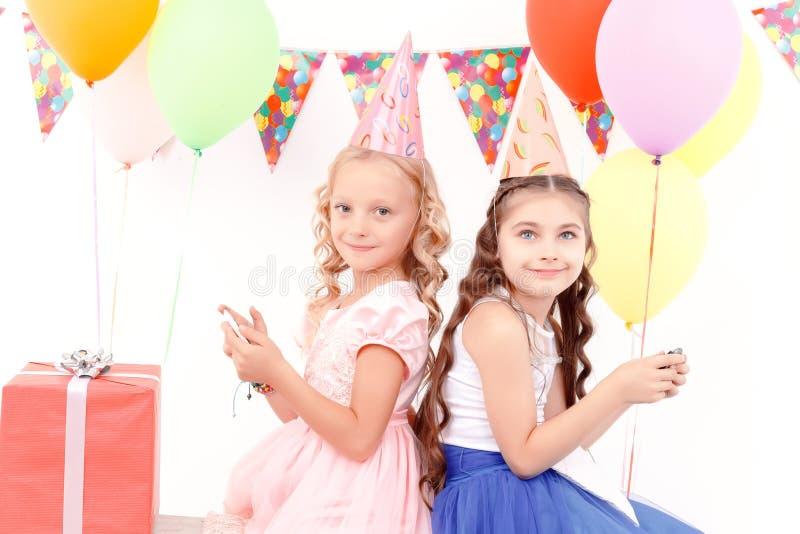 Twee meisjes met mobiele telefoon tijdens verjaardagspartij stock fotografie