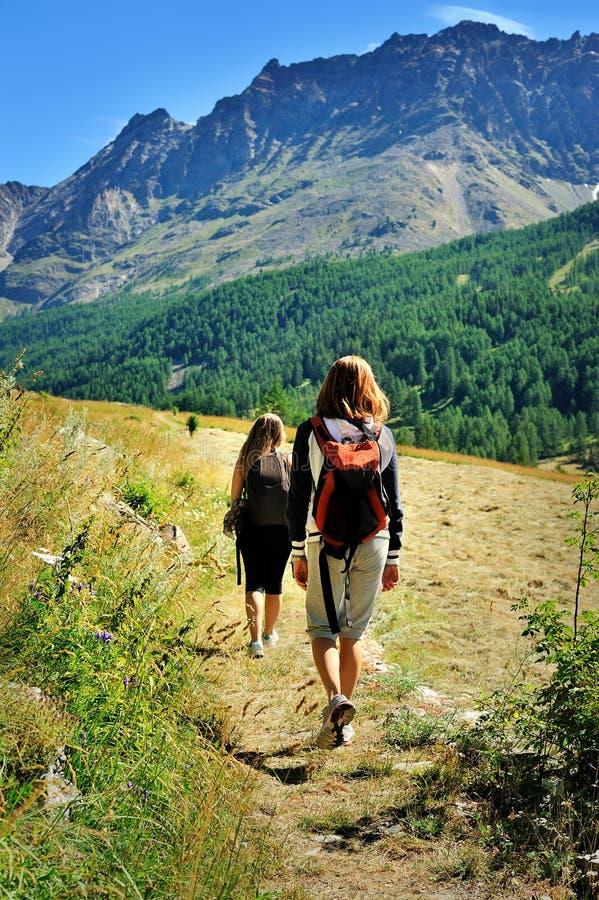 Twee meisjes met rugzakken in de toerismecampagne van de Alpiene bergen royalty-vrije stock fotografie