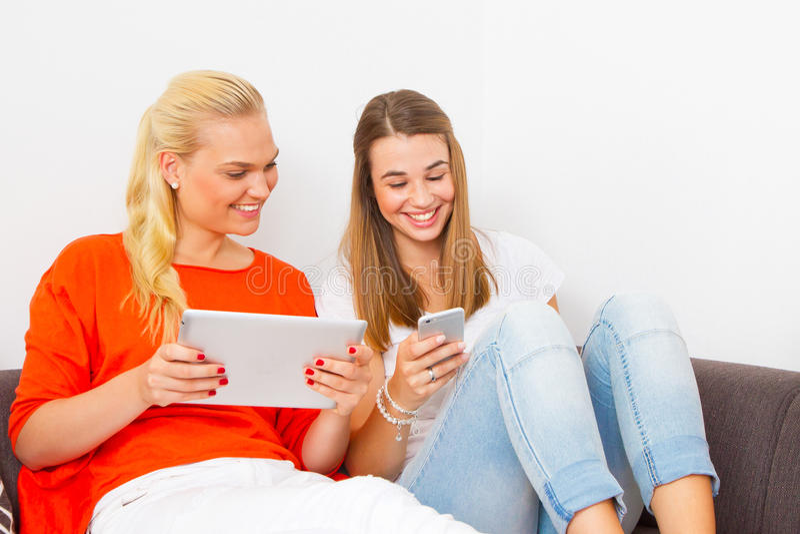 Twee meisjes met tablet en slimme telefoon stock foto's
