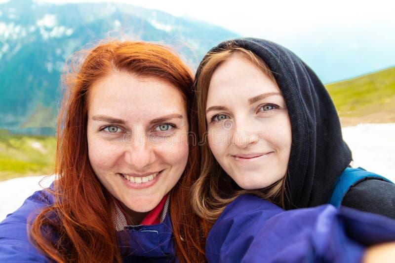 Twee meisjes nemen een beeld met hun mobiel Twee vrienden genieten in openlucht van aard en Zij zitten aan de kant van royalty-vrije stock afbeelding