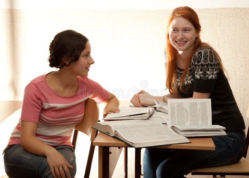 Twee meisjes nemen in een bibliotheek in dienst stock afbeelding