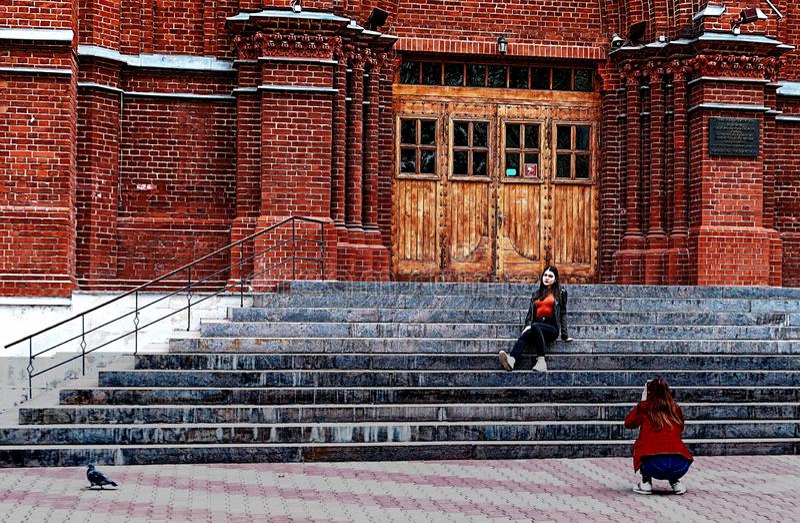 Twee meisjes nemen selfies op treden van rode katholieke kerk in Moskou stock afbeelding