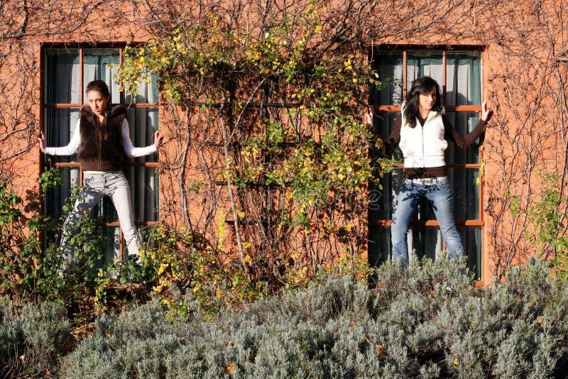 Twee meisjes op de venstervensterbank royalty-vrije stock afbeeldingen