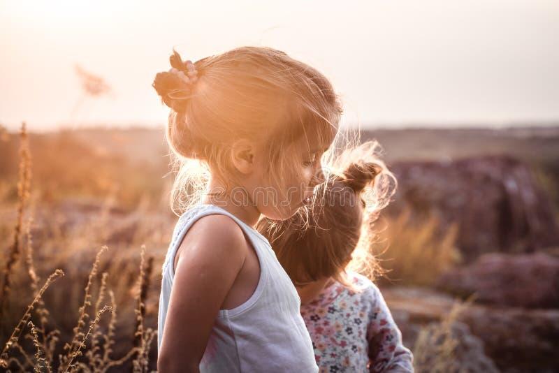 Twee meisjes op een gebied bij zonsondergang stock foto