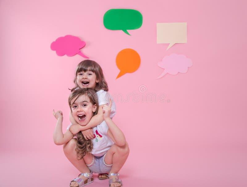 Twee meisjes op een gekleurde achtergrond met toespraakpictogrammen stock afbeeldingen