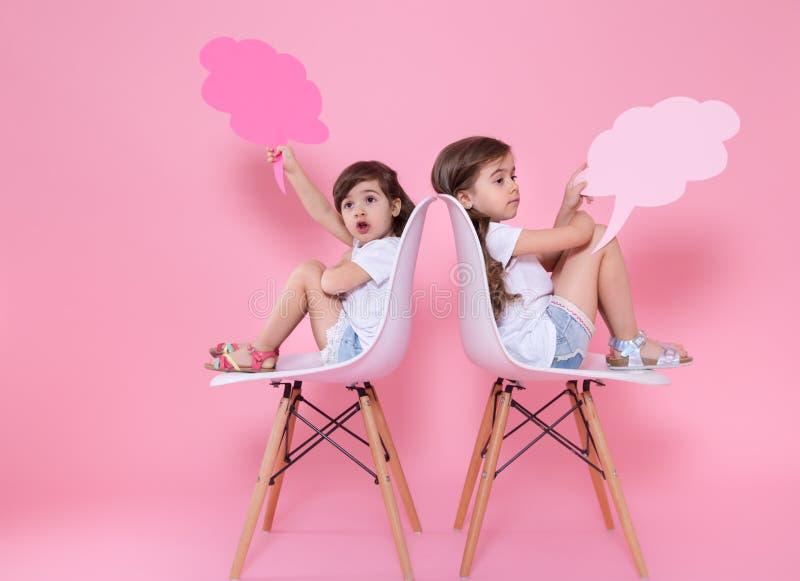 Twee meisjes op een gekleurde achtergrond met toespraakpictogrammen royalty-vrije stock afbeelding