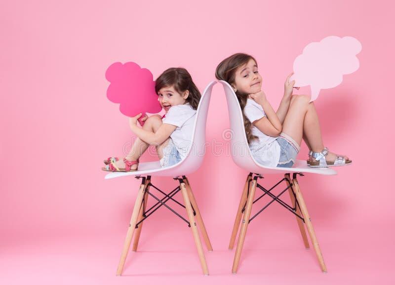 Twee meisjes op een gekleurde achtergrond met toespraakpictogrammen royalty-vrije stock afbeeldingen