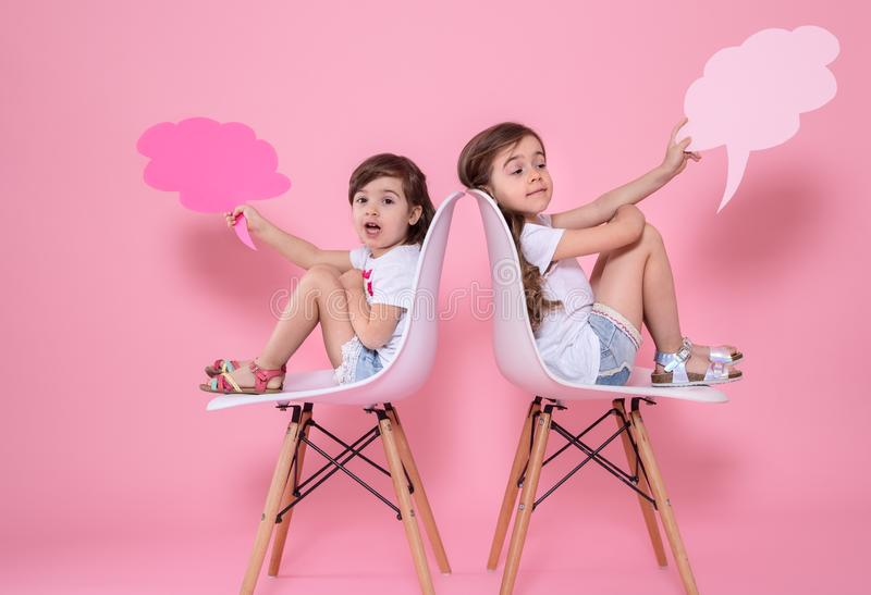 Twee meisjes op een gekleurde achtergrond met toespraakpictogrammen royalty-vrije stock foto's