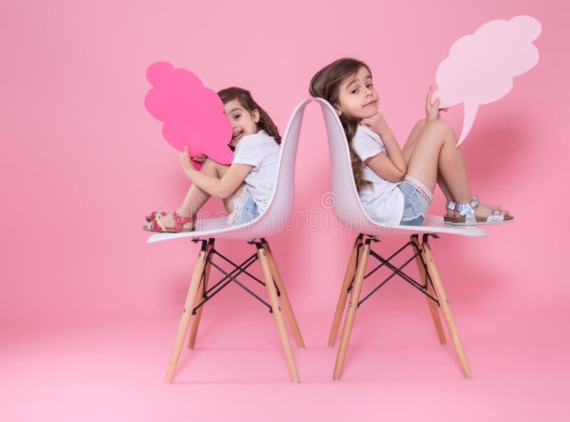Twee meisjes op een gekleurde achtergrond met toespraakpictogrammen stock foto's
