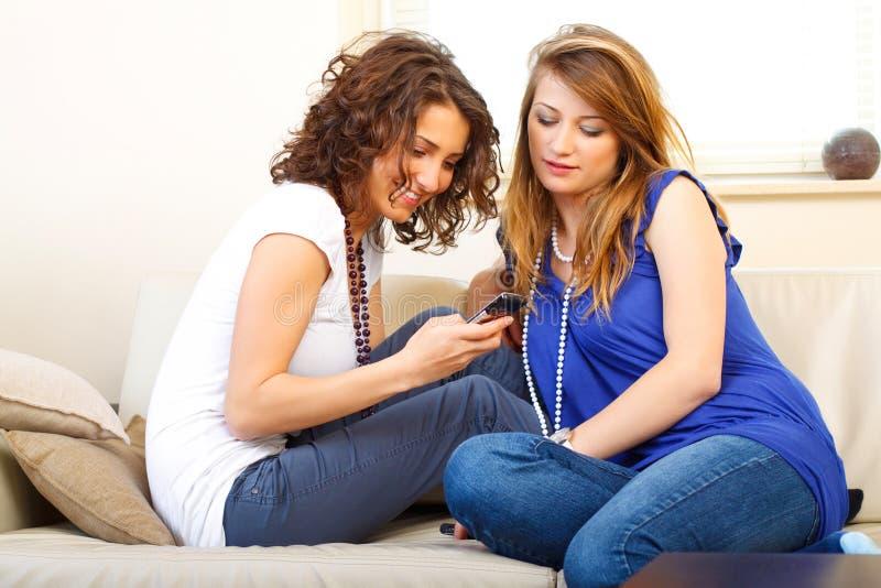 Twee meisjes op een laag die een mobiele telefoon met behulp van royalty-vrije stock fotografie