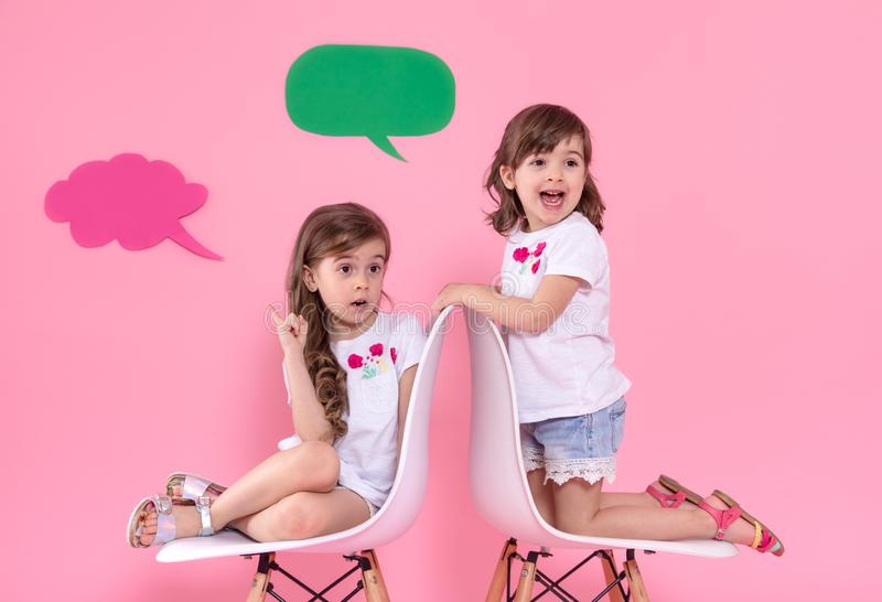 Twee meisjes op gekleurde achtergrond met toespraakpictogrammen royalty-vrije stock afbeelding