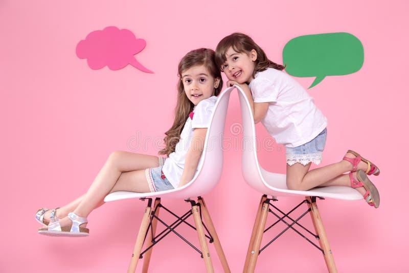 Twee meisjes op gekleurde achtergrond met toespraakpictogrammen royalty-vrije stock foto's