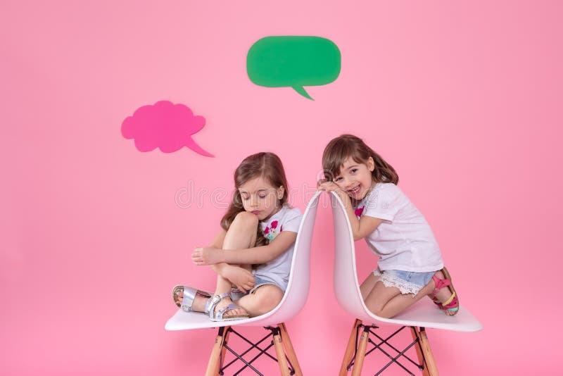 Twee meisjes op gekleurde achtergrond met toespraakpictogrammen stock foto