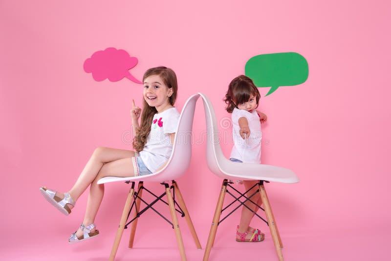 Twee meisjes op gekleurde achtergrond met toespraakpictogrammen stock foto's