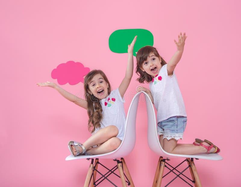 Twee meisjes op gekleurde achtergrond met toespraakpictogrammen royalty-vrije stock fotografie