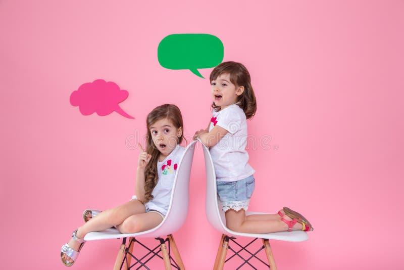 Twee meisjes op gekleurde achtergrond met toespraakpictogrammen stock afbeelding