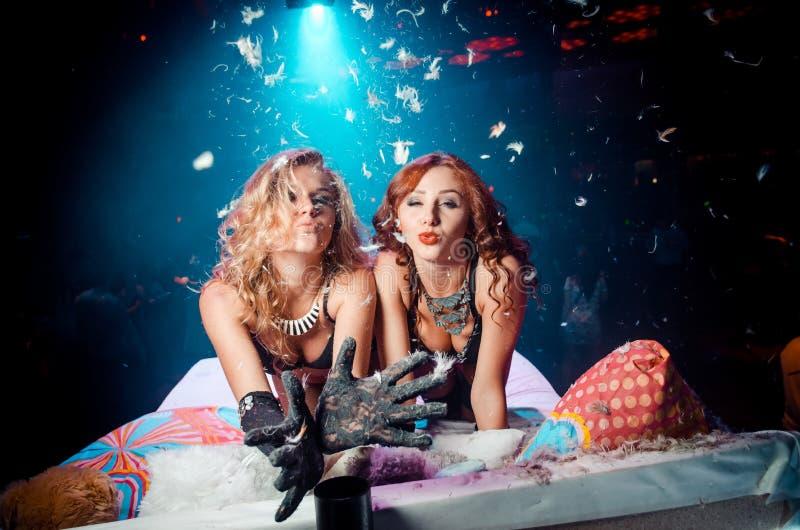 Twee meisjes op het bed die lucht verzenden kussen stock foto