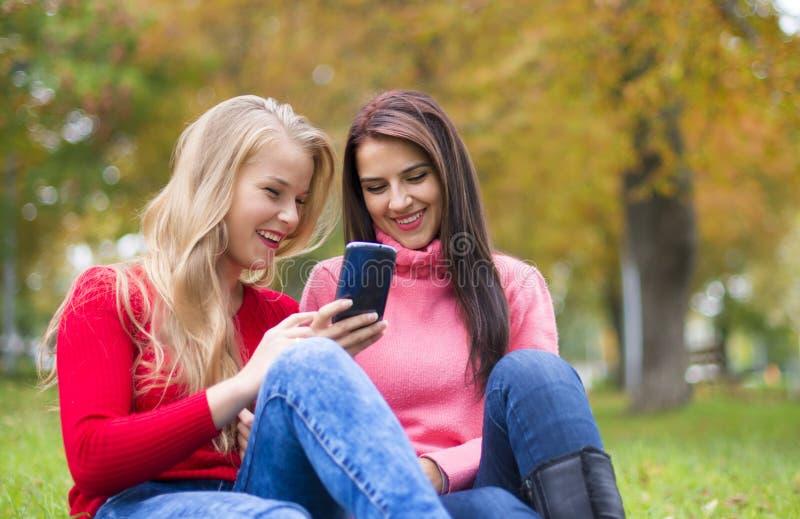 Twee meisjes in park met een mobiele telefoon in de herfst royalty-vrije stock foto