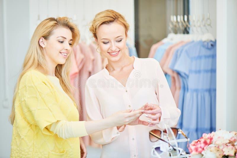 Twee meisjes proberen in een kledingsopslag royalty-vrije stock fotografie
