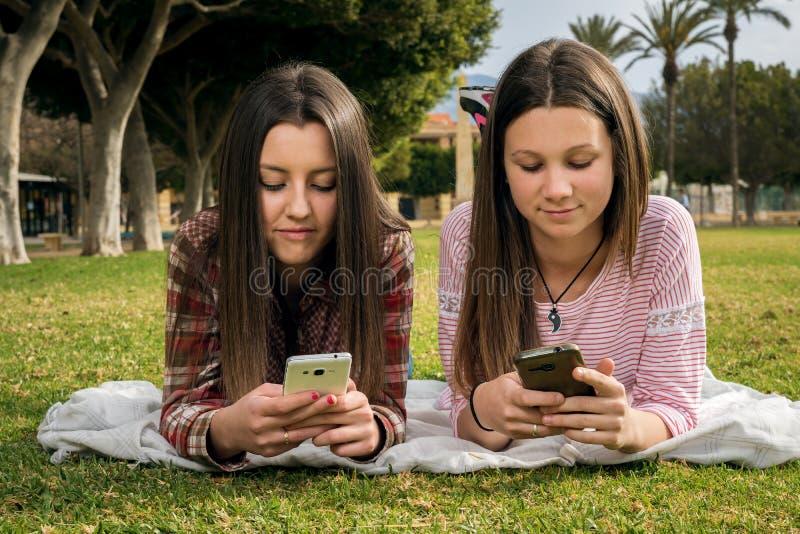 Twee meisjes schrijven in mobiele telefoons stock foto